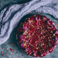 persian love cake with red glaze next to gauzy fabric