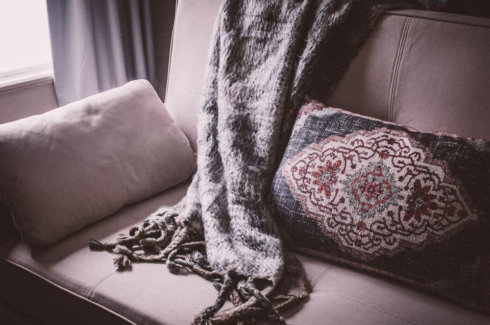 an organic sofa bed with a throw and bohemian pillow