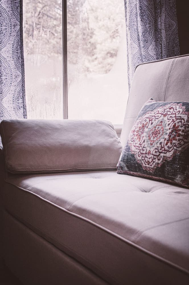 a white sofa lit by window light