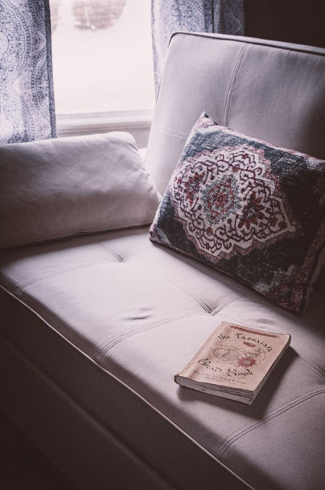 a white organic sofa bed with bohemian pillow and tassajara bread book by window light