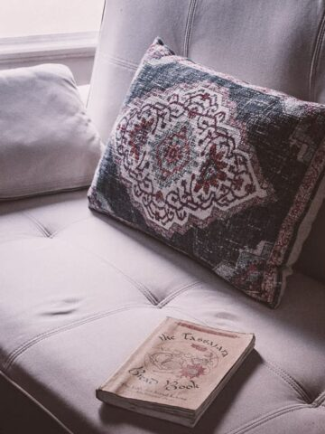 an image of a non toxic white sofa bed lit by window light with a book and pillow resting on top