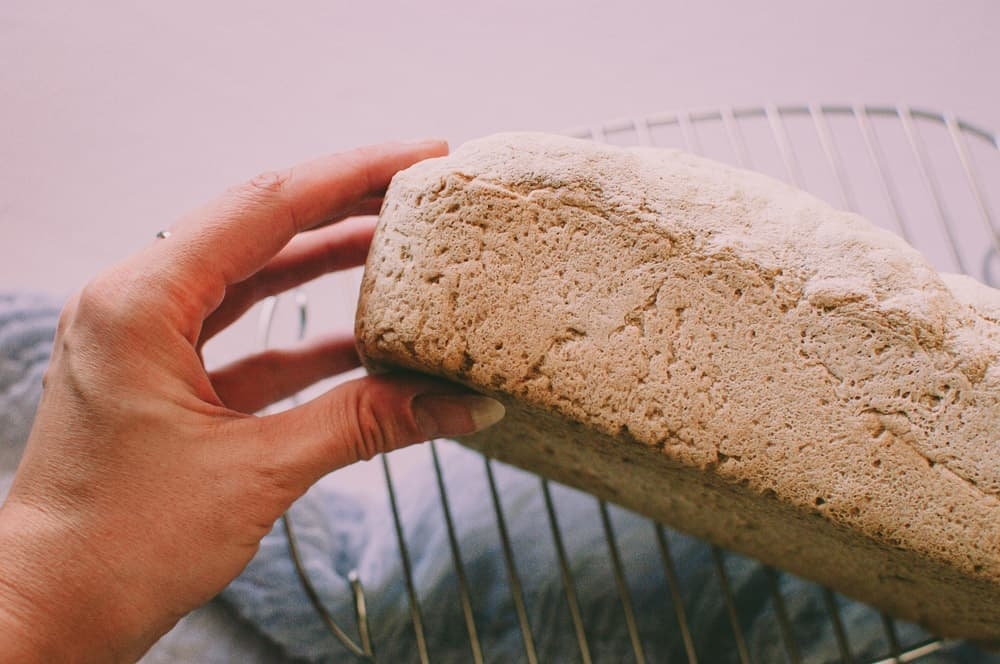 a hand holding a fresh loaf of vegan gluten free bread