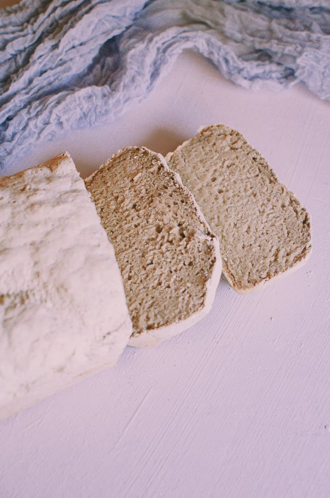 a cut loaf of vegan gluten free bread next to purple table runner