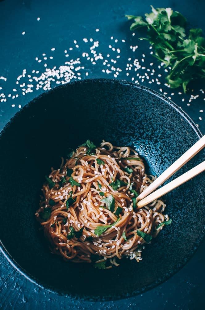 black ceramic bowl filled with sesame ramen noodles chopsticks cilantro