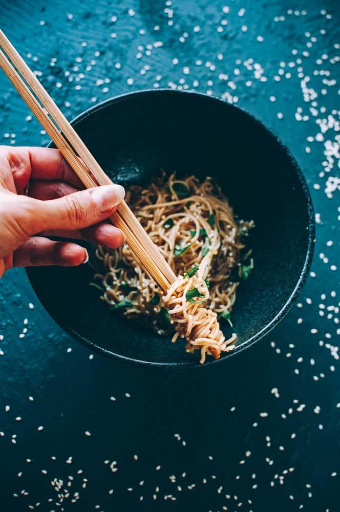 hand holding chopsticks over bowl filled with sesame noodles