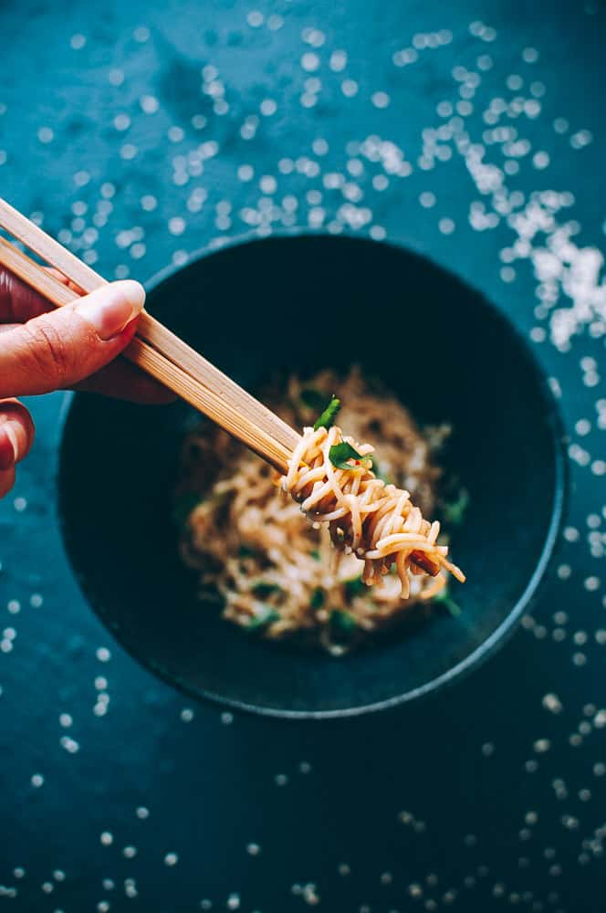 hand holding chopsticks wrapped in noodles