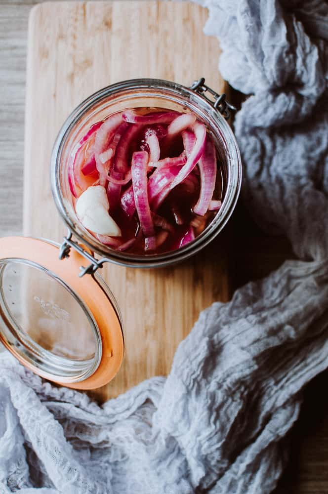 an open jar of pickled red onions resting a wooden cutting board