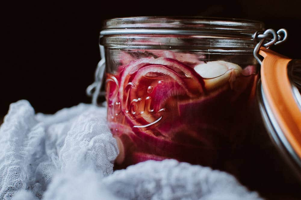 a side shot of a jar filled with pickled red onions