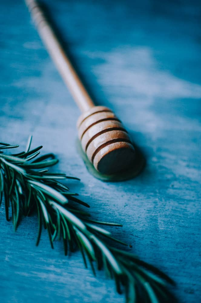 a wooden honey spoon dipped in honey laying next to a sprig of fresh rosemary