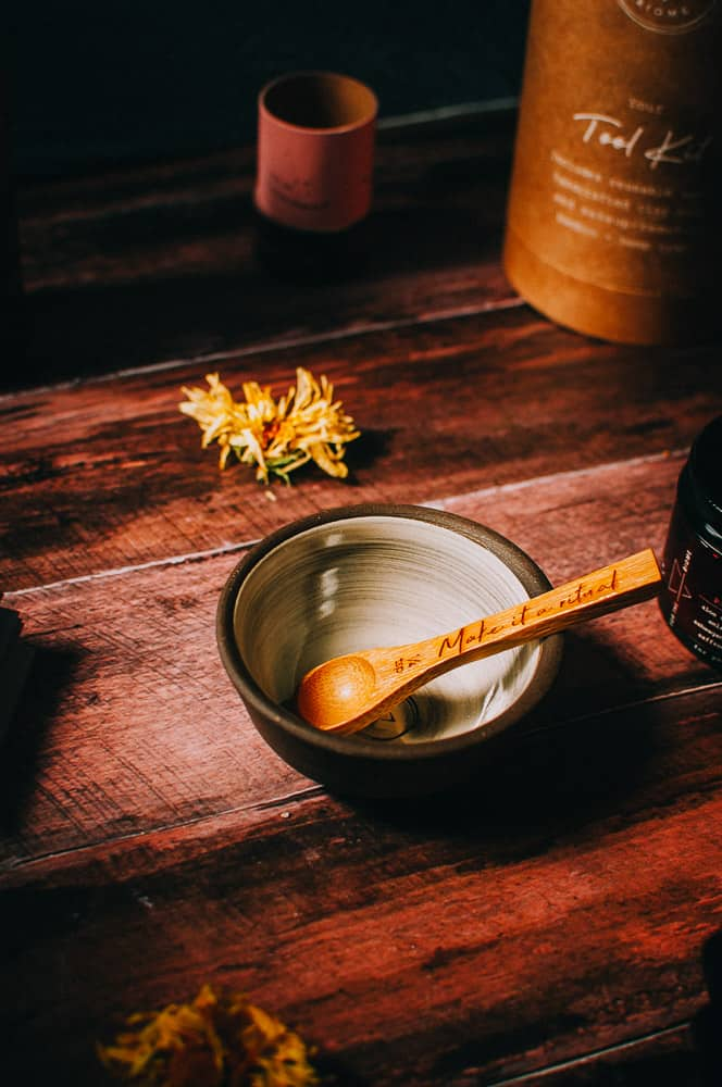 a ceramic bowl and wooden spoon lit by golden light