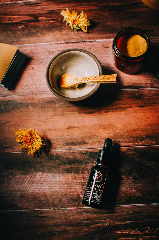 sunlight hitting a ceramic bowl wooden spoon yellow flower and for the biome skincare products arranged on wooden background