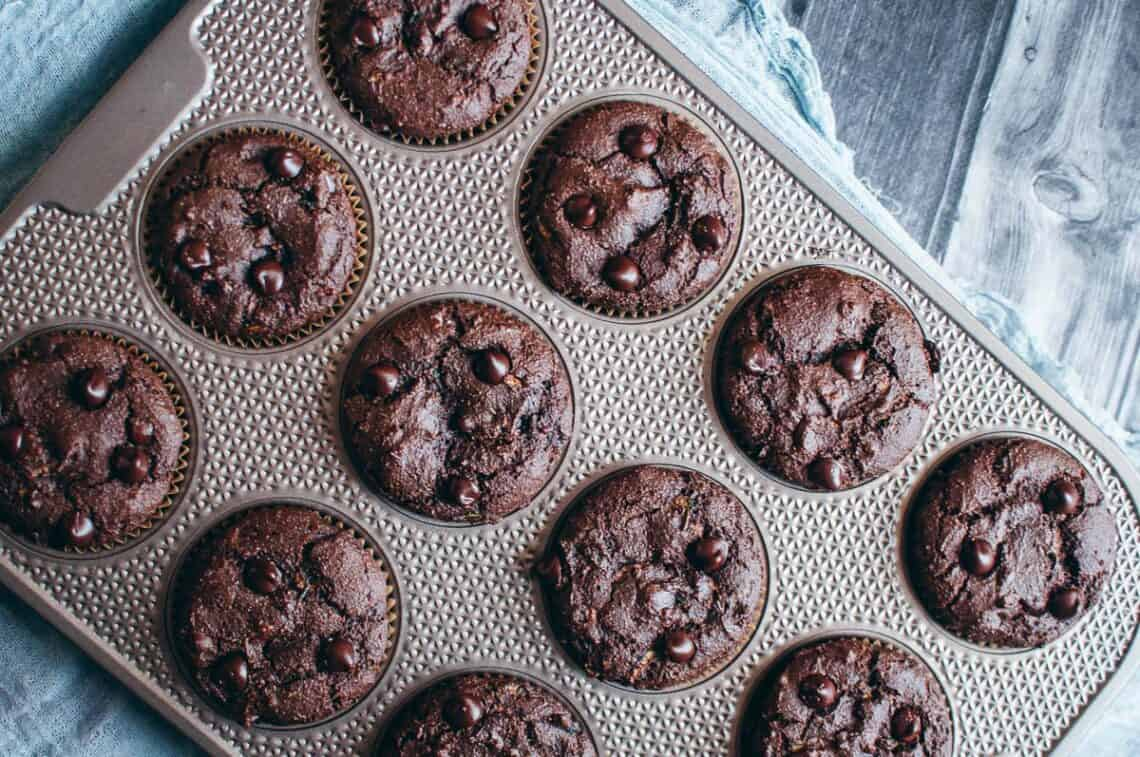 a muffin tin filled with chocolate muffins top view