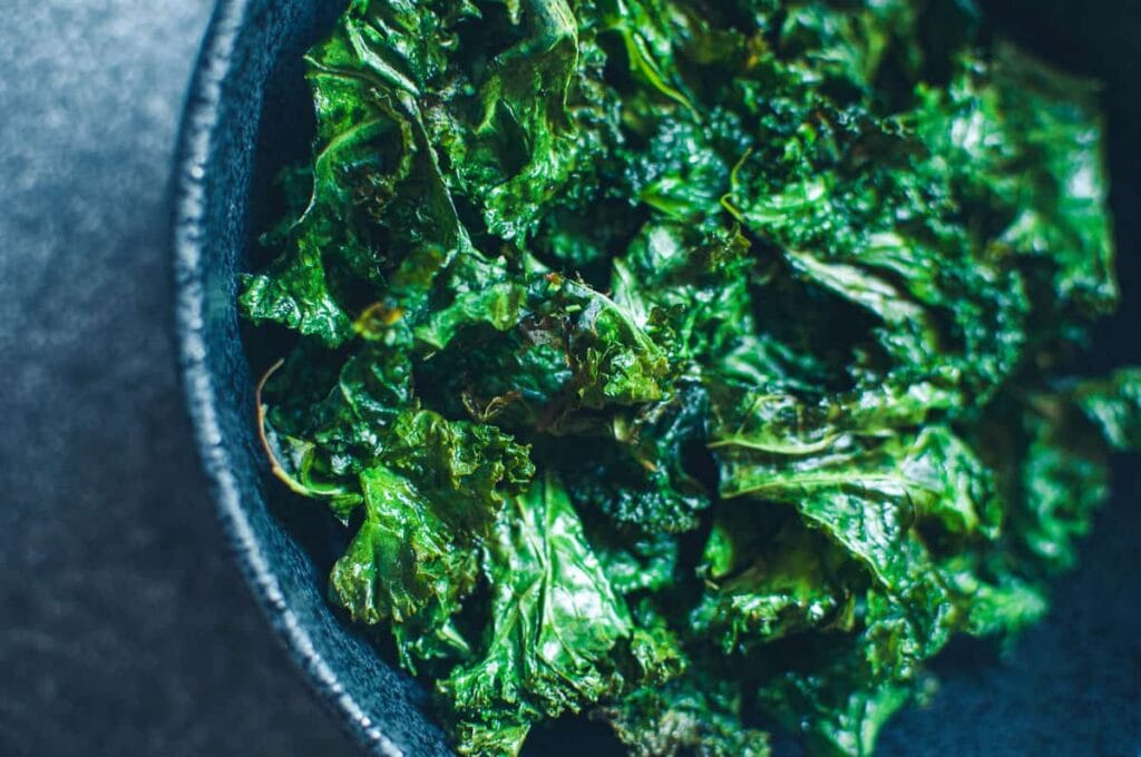 a close up of a bowl of air fryer kale chips