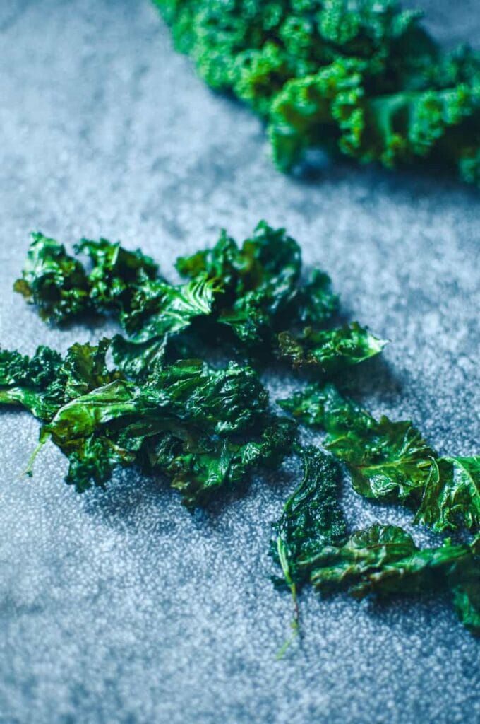 a bunch of kale chips on grey background