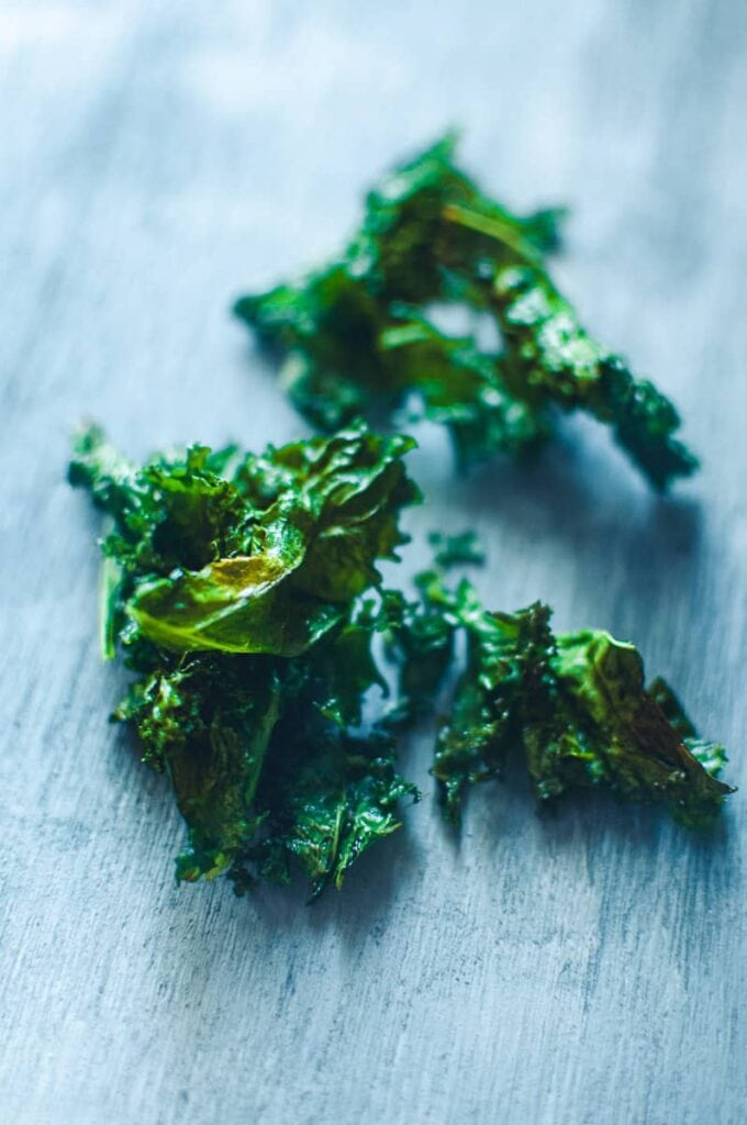 freshly air fired kale chips resting on a table