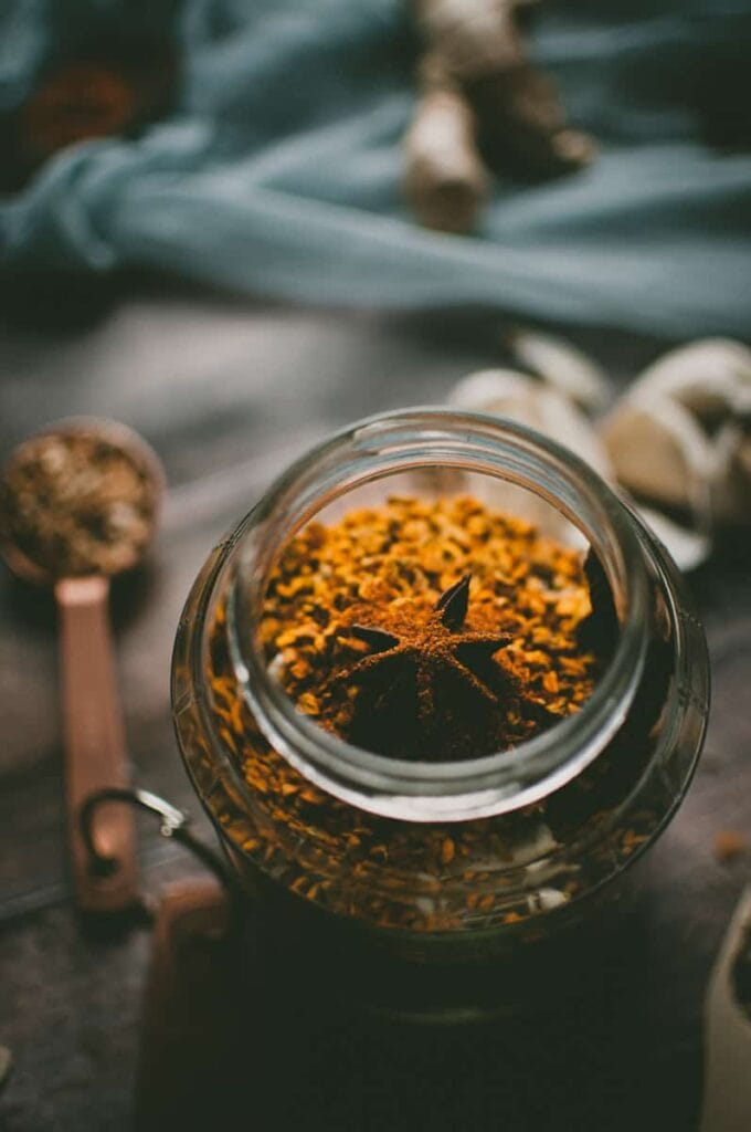 a star anise pod rest on a jar of turmeric root