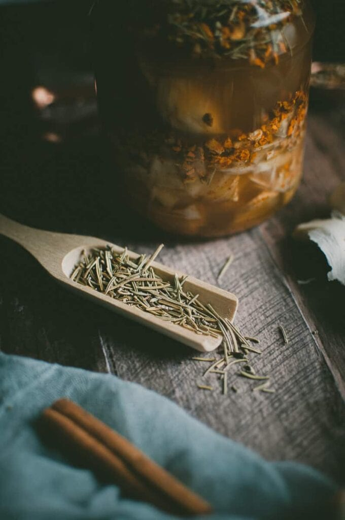 a wooden spoon filled with dried rosemary