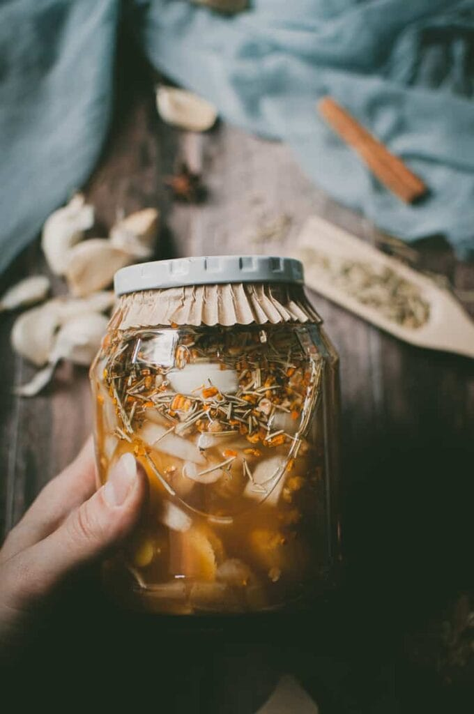 a hand holding a jar of fire tonic