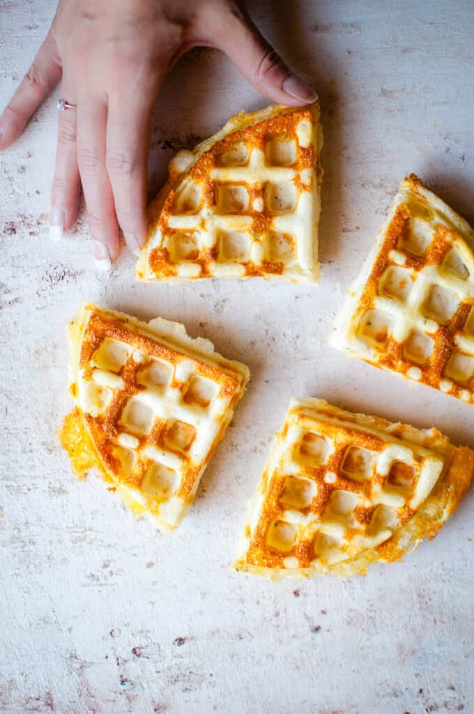 4 cheesy waffles with a hand reaching for them