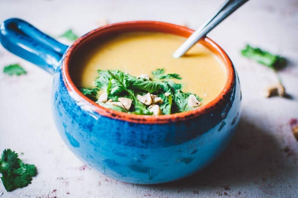 a blue crock full of soup topped with cilantro and cashews