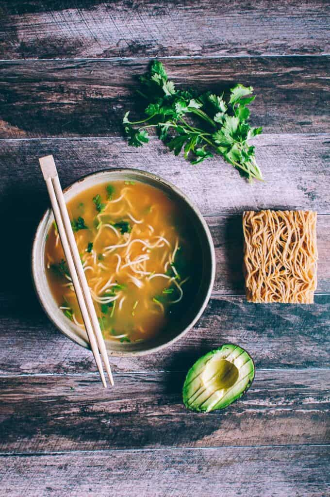 a bowl of pho on a wooden backdrop