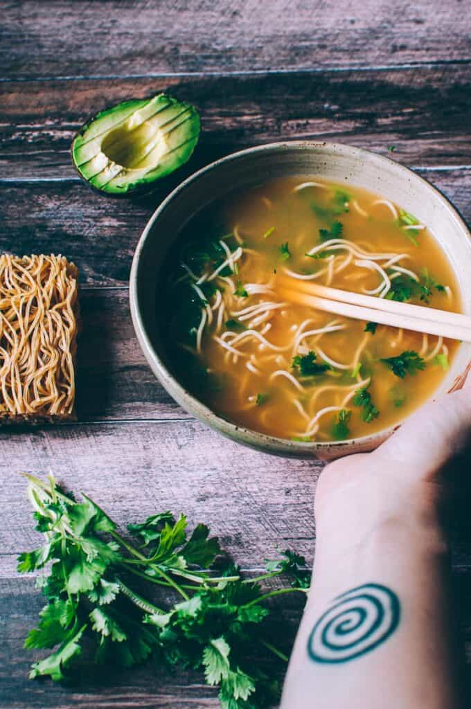 a bowl of ramen pho with avocado and cilantro by side