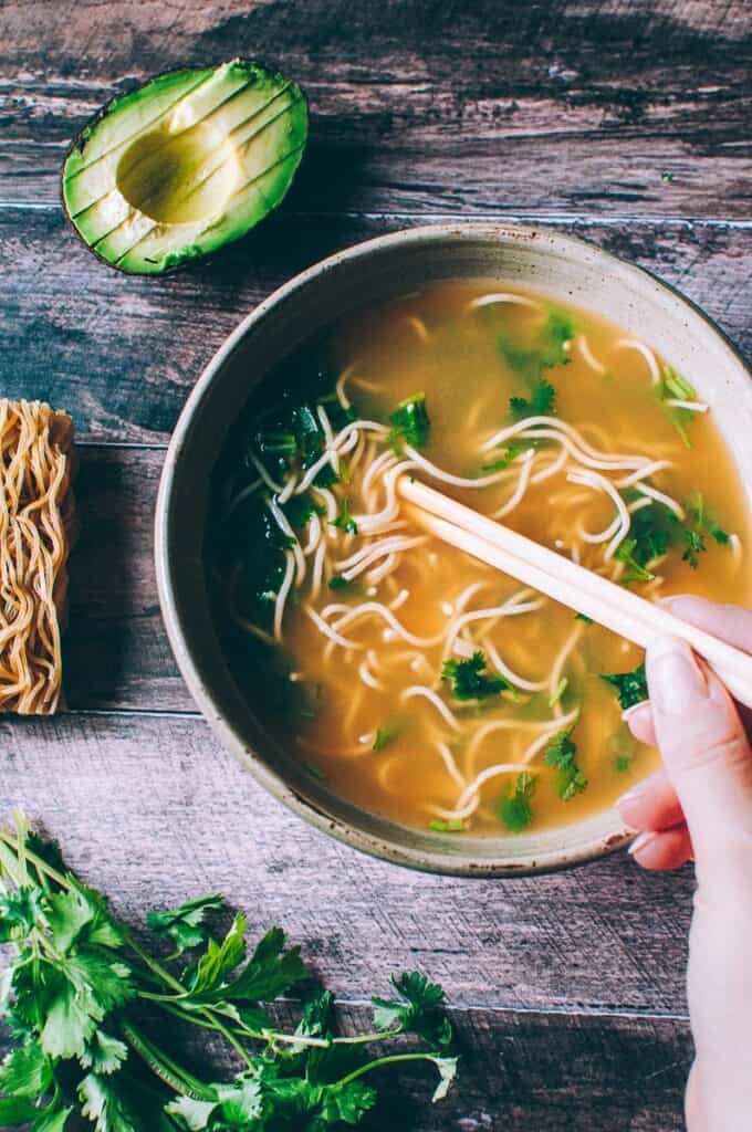 a hand holding chopsticks in a bowl of pho with ramen noodles