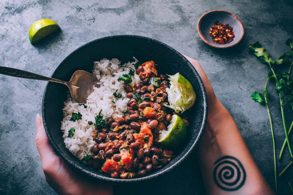 hands holding a black bowl filled with rice and adzuki beans