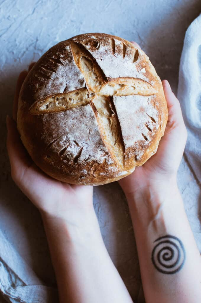 hands holding a loaf of gluten free sourdough bread