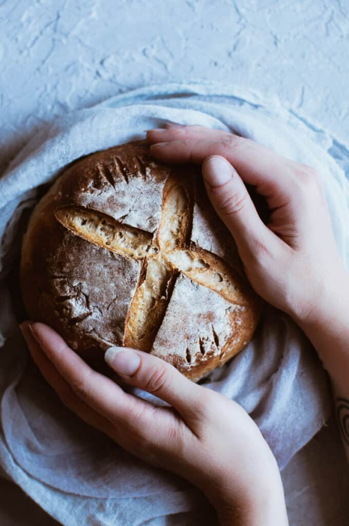 hands holding a rustic bread boule