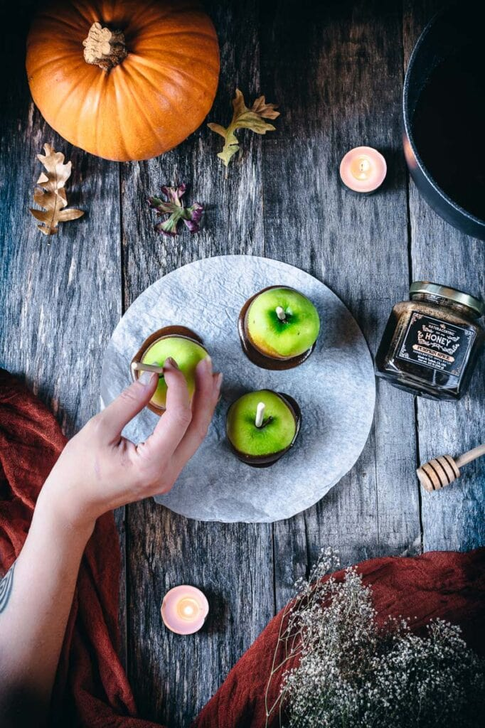 a hand reaching for a caramel apple amidst a wooden backdrop