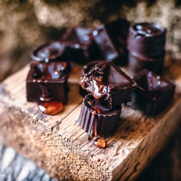 a wooden block topped with honey filled chocolates