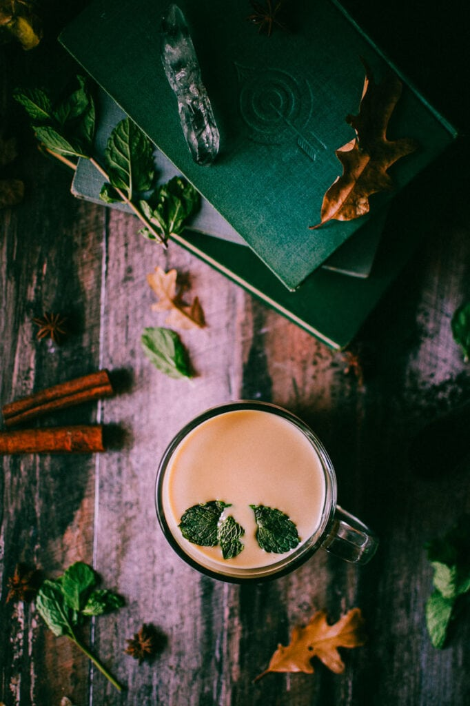 a top shot flatlay of chai leaves cinnamon books and crystals
