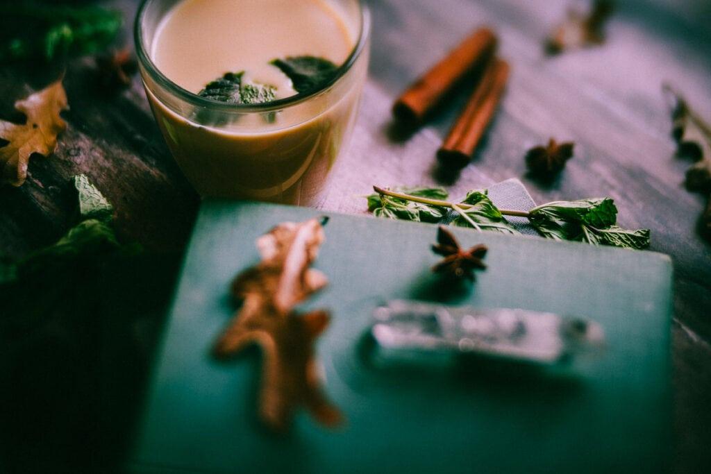 a dreamy hazy shot a book crystal dry leaves and a mug of mint chai