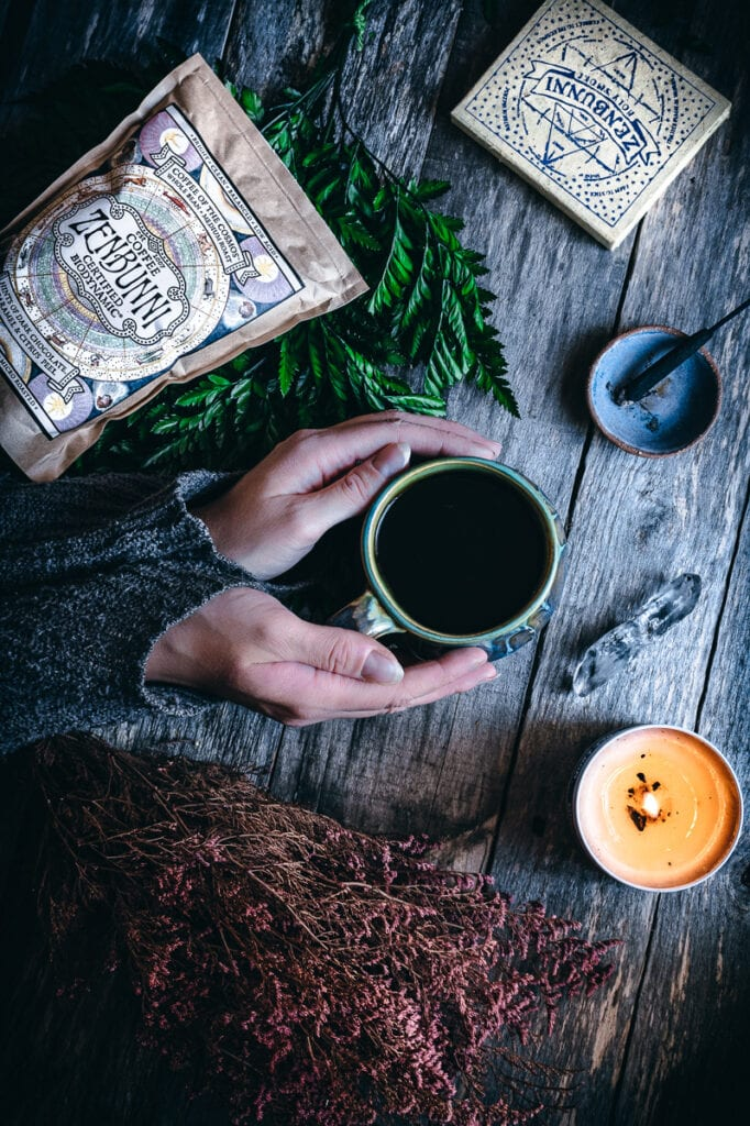 a flatlay of hands holding a coffee cup on a wooden table next to lit incense