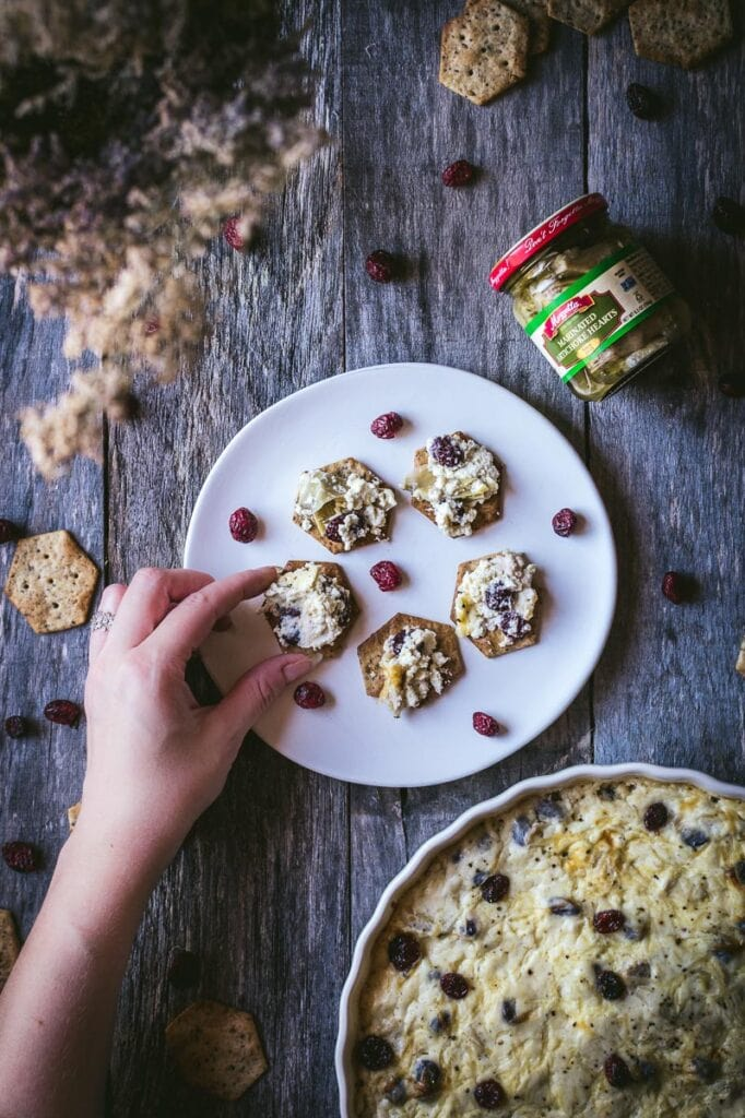 a flatlay style photograph of mezzetta artichoke hearts and crackers topped with festive hot artichoke cranberry dip