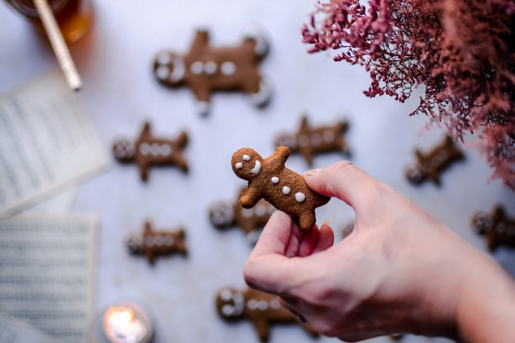 a hand holding a gingerbread man above a blurry background with music sheet book pages