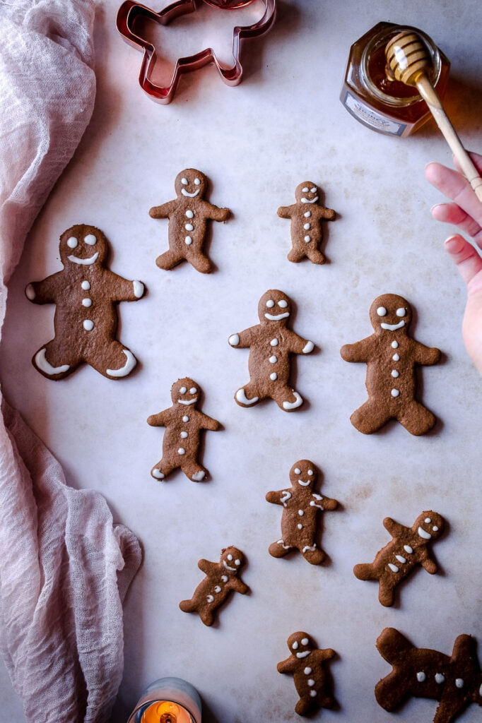 a hand holding a honey spoon on the edge of a collection of gluten-free gingerbread men
