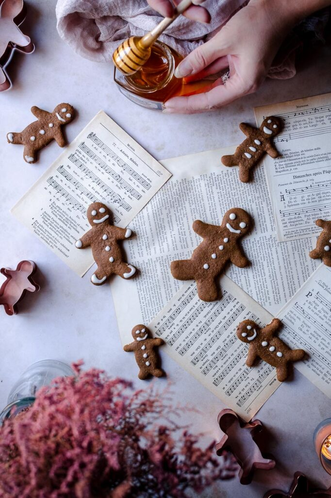 a hand holding a honey spoon dripping with honey next to music sheets and gluten free gingerbread men cookies
