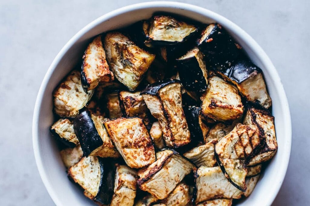 a white bowl filled with air fried eggplant