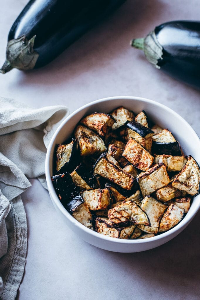 air fryer eggplant in white bowl with a napkin and purple eggplant in background