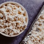 a white bowl filled with popcorn next to an air fryer tray filled with popcorn