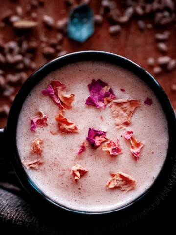 a mug of pink moon milk topped with rose petals