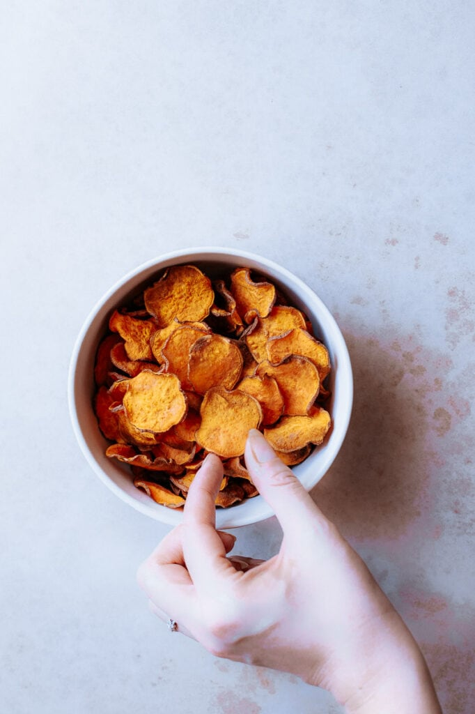 a hand reaching out to grab a sweet potato chip