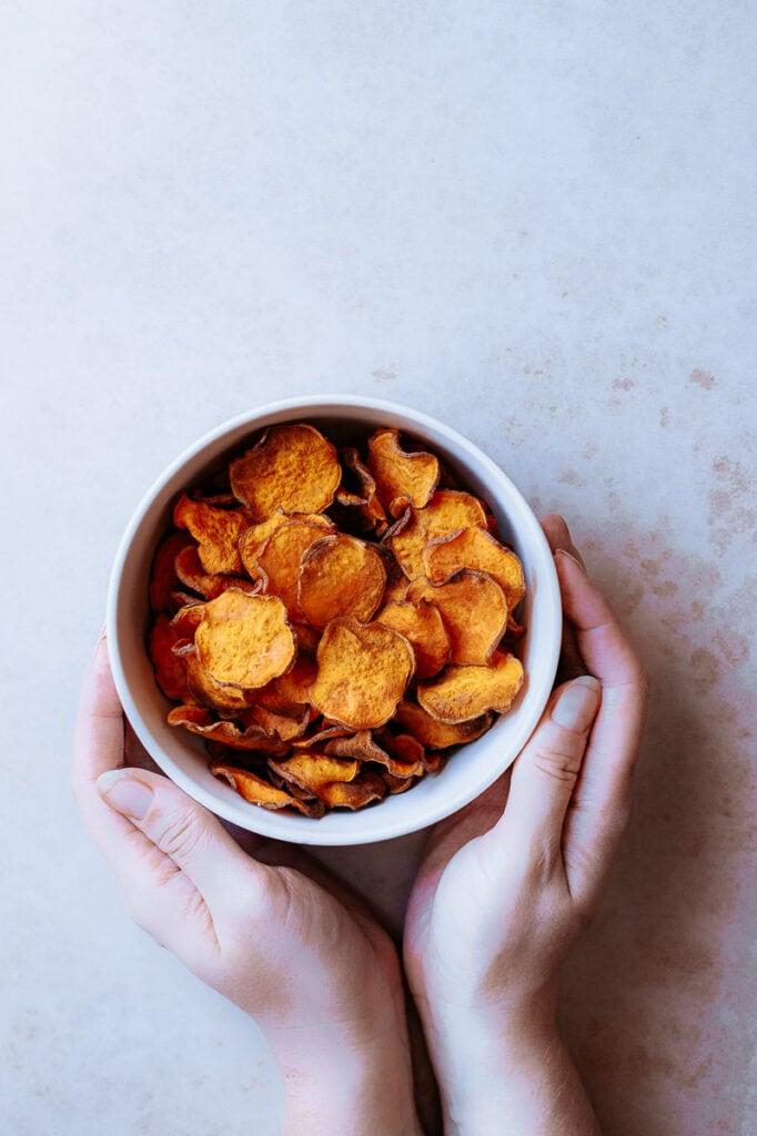 hands holding a bowl of orange chips