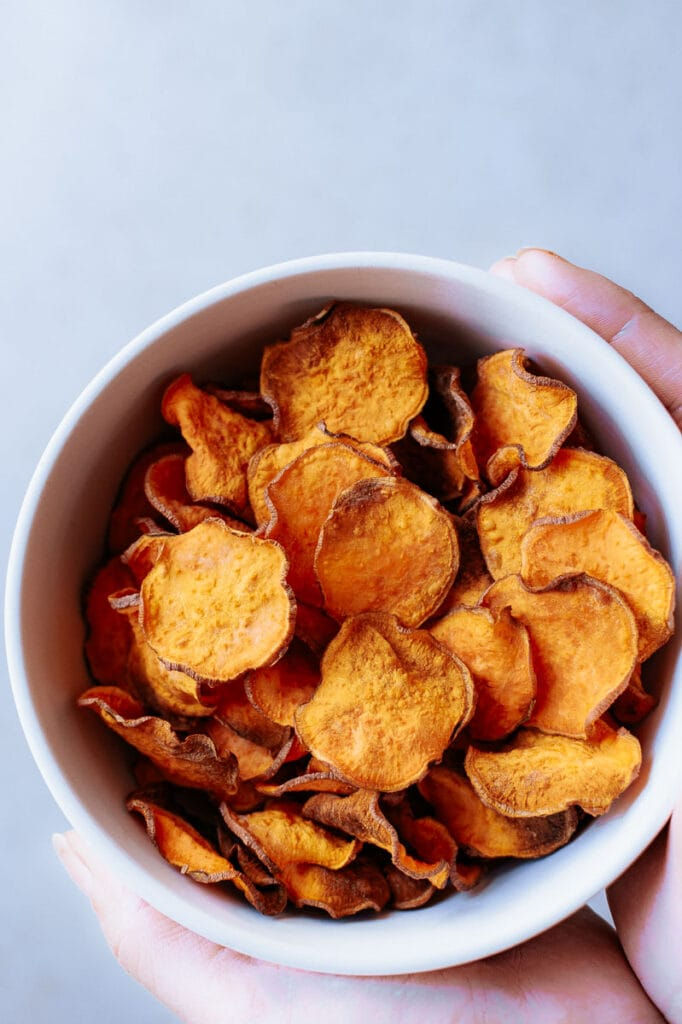 hands holding a bowl filled with veggie chips