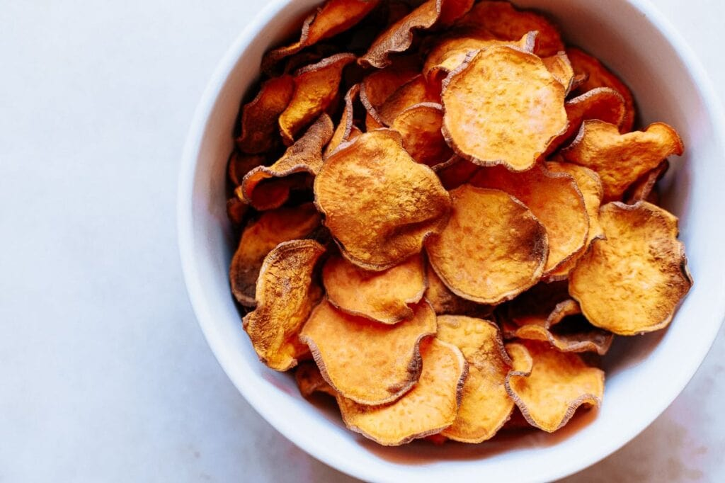 a white bowl filled with vibrant orange sweet potato chips
