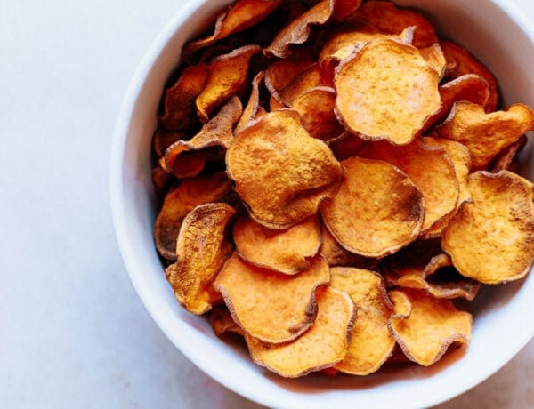 a white bowl filled with vibrant sweet potato chips