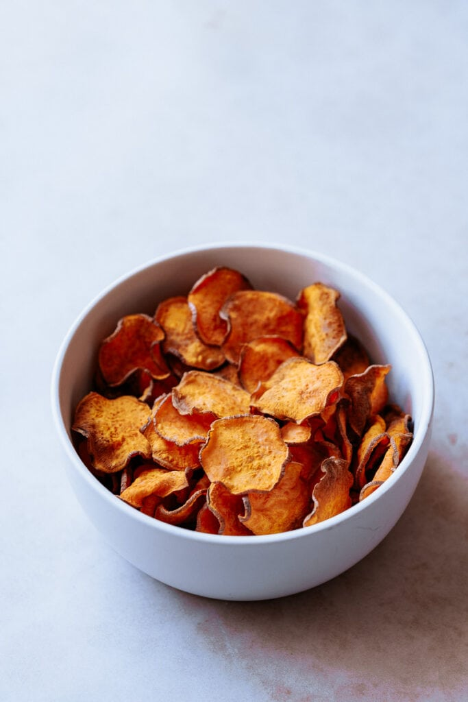 a white bowl filled with air fried sweet potato chips