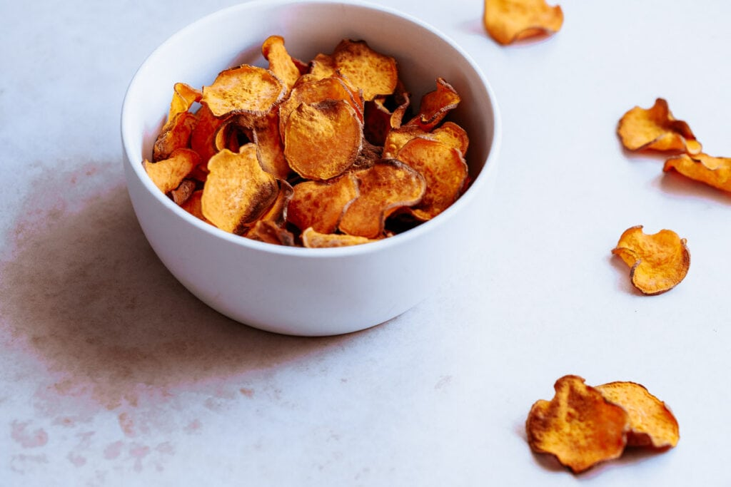 a white bowl filled with air fryer sweet potato chips